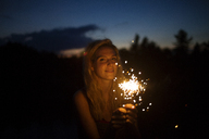 Portrait of smiling woman holding sparklers at night - CAVF17666