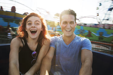 Young couple enjoying ride in amusement park against sky - CAVF17672