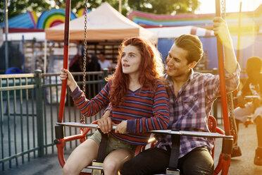 Young couple enjoying ride at amusement park - CAVF17678