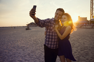 Young couple taking selfie while standing on sand during sunset - CAVF17681