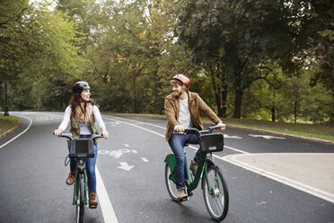 Smiling couple riding bicycle on road at park - CAVF17753