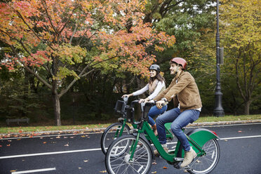 Smiling couple riding bicycle at park - CAVF17756