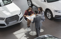 Car salesman watching couple customers signing financial contract paperwork in car dealership showroom - CAIF20047