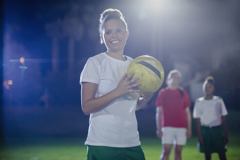 Portrait smiling, confident young female soccer player holding soccer ball on field at night - CAIF20107
