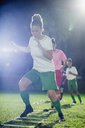 Young female soccer players practicing agility sports drill on field at night - CAIF20110