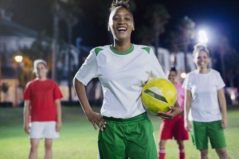 Portrait confident, laughing young female soccer player practicing on field at night - CAIF20113