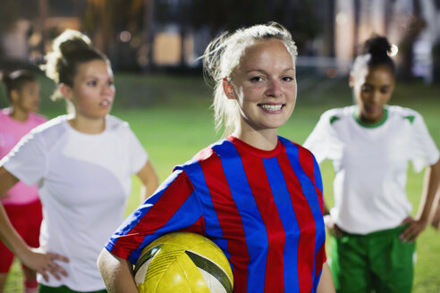 Portrait smiling, confident young female soccer player with ball on field at night - CAIF20116