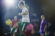 Young female soccer player kicking the ball, practicing on field at night - CAIF20119