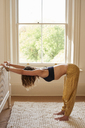 Woman practicing yoga tabletop stretch, stretching arms and back in bedroom - CAIF20128