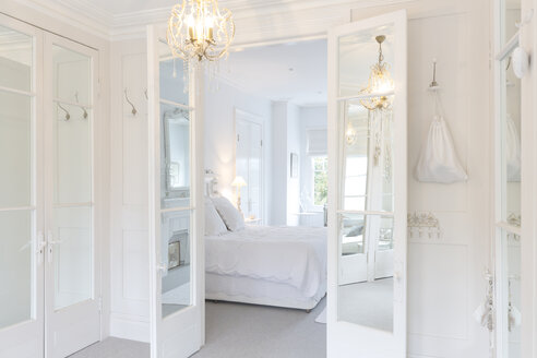 White, luxury home showcase interior bedroom with French doors and chandelier - CAIF20140
