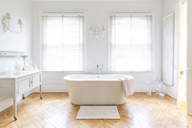 White, luxury home showcase bathroom with soaking tub and parquet hardwood floor - CAIF20149