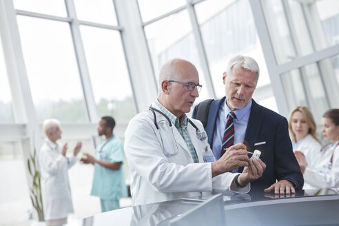 Male doctor and pharmaceutical representative discussing medication in hospital lobby - CAIF20185