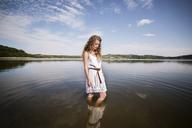 Woman standing in lake against sky - CAVF17827