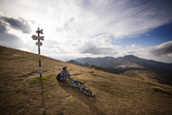 Male backpacker sitting on mountain by bicycle against cloudy sky - CAVF17893