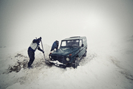 Men removing snow with shovel by car - CAVF17938
