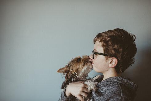 Yorkshire Terrier licking boy's face against wall at home - CAVF18025