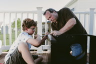 Father and son using screw driver while making metallic cabinet on porch - CAVF18037