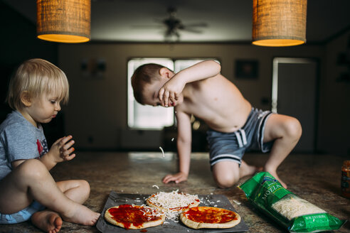 Boy putting cheese on pizza bread while sitting with brother at home - CAVF18109