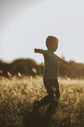 Full length of boy playing on grassy field - CAVF18136