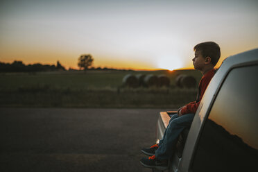 Side view of boy looking away while sitting on pick-up truck during sunset - CAVF18145