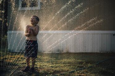 Boy enjoying water from sprinkler while standing in backyard - CAVF18148