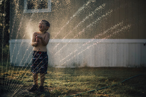 Boy enjoying water from sprinkler while standing in backyard - CAVF18148