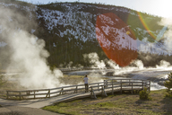 Mid distance of hiker looking at steam coming out from hot spring at Yellowstone National Park - CAVF18193