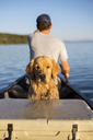 Portrait of dog with man traveling in boat on lake at Grand Teton National Park - CAVF18286