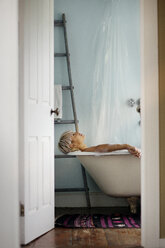Side view of woman relaxing in bathtub at home - CAVF18901