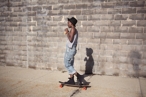 Side view of woman drinking smoothie while standing on skateboard - CAVF19000