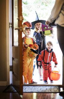 Cheerful siblings dressed for Halloween party standing at door - CAVF19051