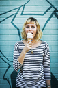 Portrait of woman eating ice cream while standing against wall - CAVF19087