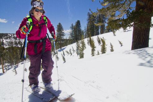 Female skier walking on snow field - CAVF19285