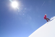 Low angle view of female snowboarder descending from snow field against clear sky - CAVF19288