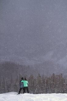 Rear view of friends standing on snowy landscape against sky - CAVF19375