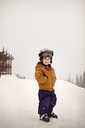 Portrait of smiling boy standing on snow field against sky - CAVF19384