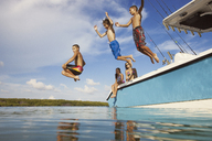 Low angle view of happy boys jumping from boat at sea against sky - CAVF19717