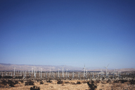 Wind turbines on field against clear blue sky - CAVF19735