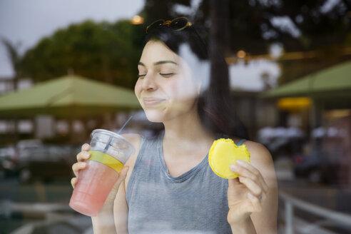 Happy woman drinking juice seen from glass window - CAVF19783