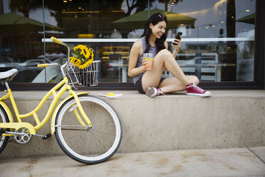 Happy woman using phone while sitting on retaining wall by bicycle - CAVF19786