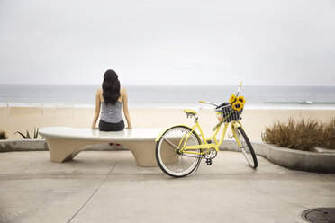 Rear view of woman looking at beach while sitting on bench by bicycle - CAVF19792