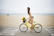 Side view of woman wearing bikini riding bicycle on street by beach - CAVF19801