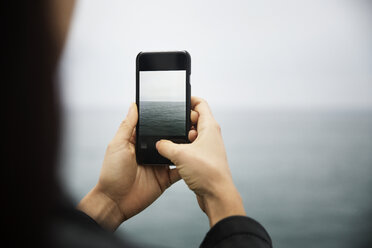 Cropped image of woman photographing sea through mobile phone - CAVF19810