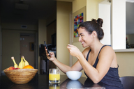 Smiling woman using smart phone while eating breakfast on table at home - CAVF19840