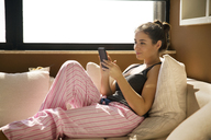 Side view of woman using smart phone while sitting on sofa at home - CAVF19843