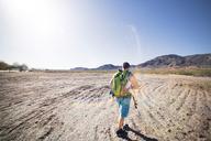 Rear view of hiker walking on field against clear blue sky - CAVF19885
