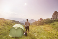 Rear view of hiker standing by tent on hill against sky - CAVF19900