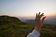 Optical illusion of hand holding sun on hill during sunset - CAVF19903