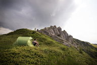 Low angle view of hiker sitting by tent on mountain against cloudy sky - CAVF19906