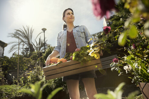 Low angle view of thoughtful woman carrying crate full of freshly harvested vegetables at organic farm - CAVF19957